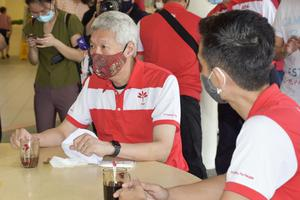 Lee Hsien Yang, left, brother of Singapore prime minister Lee Hsien Loong, meets with opposition party's candidates in Singapore (Risa Suzuki/AP)