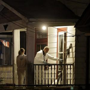 Investigators at a house in Cleveland where police say three women were found (AP/Mark Duncan)
