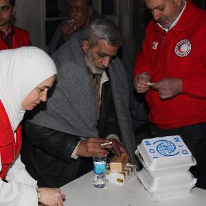 Syrian Arab Red Crescent members give food and drink to a man before he leaves the battleground city of Homs (AP)