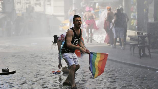 A marcher in the Gay Pride rally in Istanbul reacts as others flee after Turkish police use a water canon to disperse them (AP)