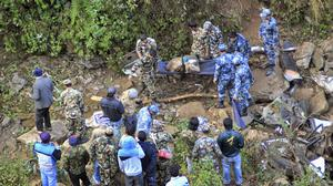 Nepalese security officers look for survivors in the wreckage of a bus after an accident 250 miles north west of Katmandu