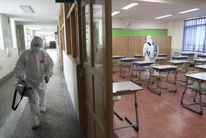 Workers wearing protective gear disinfect a school (Jo Jung-ho/AP)