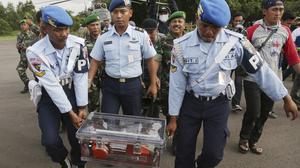 Indonesian air force personnel carry the flight data recorder of the ill-fated AirAsia Flight 8501 that crashed in the Java Sea, at the airport in Pangkalan Bun (AP)