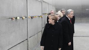 Chancellor Angela Merkel looks to the wall after she put a flower in a crack of the former Berlin Wall at the Berlin Wall memorial site at Bernauer Strasse (AP)