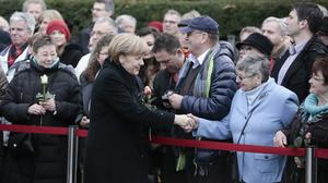 Angela Merkel shakes hands with people prior to a ceremony at the Berlin Wall memorial site at Bernauer Strasse in Berlin (AP)