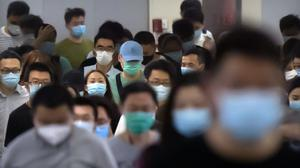 Commuters wear face masks to protect against the new coronavirus as they walk through a subway station in Beijing (Mark Schiefelbein/AP)