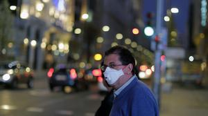 A man wears a face mask at the Gran Via avenue in Madrid (Manu Fernandez/AP)