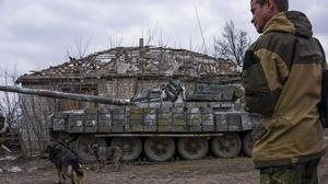 A pro-Russian rebel stands next to a tank in a village not far from Luhasnk, eastern Ukraine (AP Photo/Mstyslav Chernov)