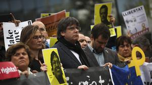 Catalonia's former regional president Carles Puigdemont, centre, holds a banner with others (Francisco Seco/AP)