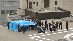 Investigators gather around the drone covered with blue sheets on the roof of prime minister Shizo Abe's official residence in Tokyo (AP)