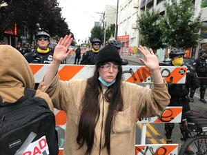 A protester stands with her hand up in front of a road blocked by Seattle police (Aron Ranen/AP)