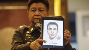 Police spokesman Lt Gen Prawuth Thavornsiri shows a photo of one of three men for whom Thai authorities have issued new arrest warrants in connection with the Bangkok bombing case (AP)