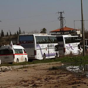 Some Syrian people on two buses followed by the Syrian Arab Red Crescent's vehicles evacuated from Homs (AP Photo)