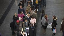People queue along a street in Madrid to buy lottery tickets (AP)