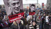 People in Moscow carry portraits of opposition leader Boris Nemtsov, who was gunned down near the Kremlin (AP)