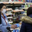 A sales clerk at a pharmacy rings up a purchase of face masks as fears of the coronavirus continues (Antonio Perez/AP)