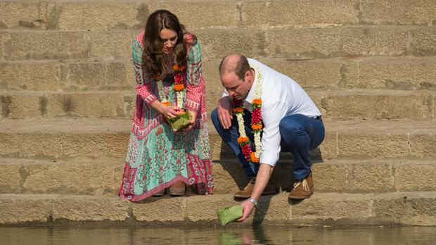The Duke and Duchess of Cambridge place flower petals in the water of the Banganga Water Tank in Mumbai
