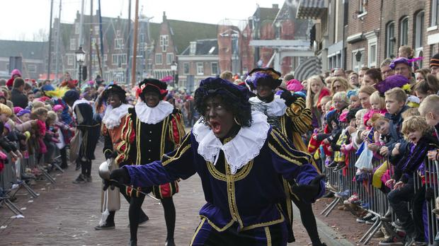 A man dressed as Black Pete jokes with children after arriving with Saint Nicholas by steamboat in Hoorn, north-western Netherlands (AP)
