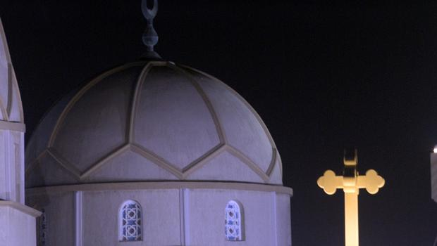 The Cross of the Great St Antony Church, right, and the dome of the Great mosque, left, are illuminated (Amr Nabil/AP)