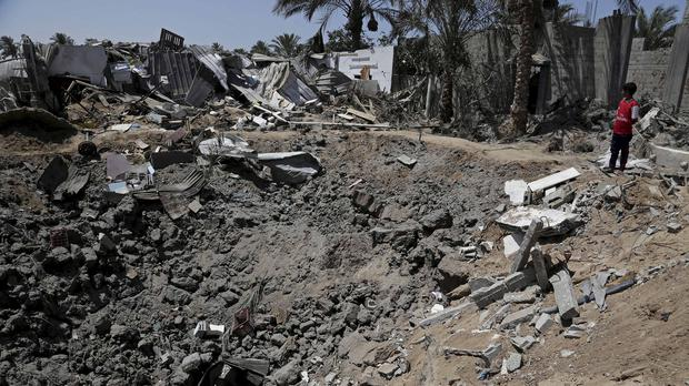 A Palestinian youth looks at damage caused by an Israeli strike in Deir el-Balah in the central Gaza Strip (AP)