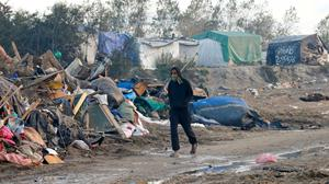 """A migrant walks past debris from makeshift shelters during the dismantlement of the camp called the """"Jungle"""" in Calais"""