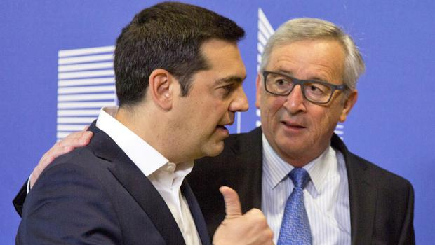 Greek Prime Minister Alexis Tsipras, left, speaks with European Commission President Jean-Claude Juncker as he arrives for a meeting prior to an EU summit in Brussels (AP)