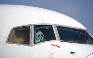 Taking no risks: A pilot wearing a protective suit parks a cargo plane at Wuhan airport. Photo: Cheng Min/Xinhua via AP