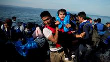 Afghans arrive on a dinghy after crossing from Turkey to Lesbos island, Greece