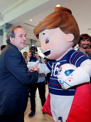 Michel Platini greets a World Cup mascot in Paris.