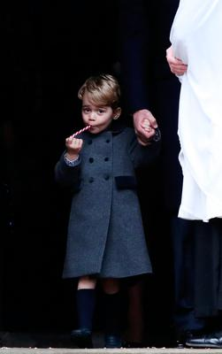 Prince George eats a sweet after attending a Christmas Day service at St Mark's Church in Englefield with his parents, Prince William and his wife Kate. Photo: Getty