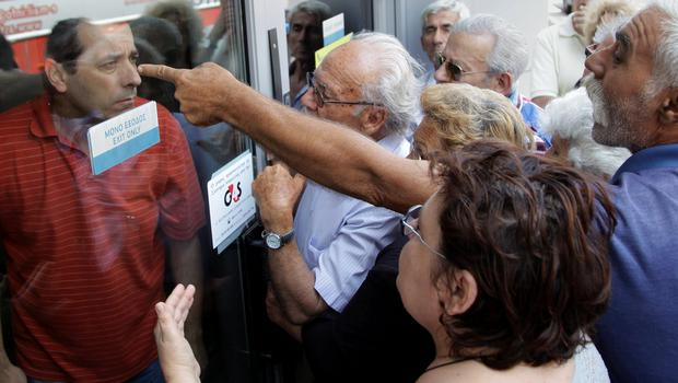Pensioners waiting outside a closed National Bank branch and hoping to get their pensions argue with a bank employee in Iraklio on the island of Crete