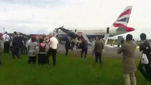 A still image taken from video shows passengers standing by a British Airways passenger jet after it made an emergency landing at Heathrow Airport west of London May 24, 2013. The plane travelling from London to Oslo was forced to make an emergency landing at Heathrow on Friday after a technical fault in an engine. REUTERS/Jon Chaplin via Reuters TV (BRITAIN - Tags: TRANSPORT SOCIETY)