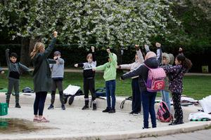 Back to school: Teacher Marie Kaas-Larsen and her pupils of the Norrebro Park primary school warm up in a Copenhagen park on Thursday after Danish pupils recently returned to lessons