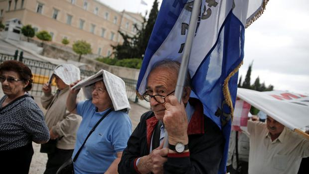 Protesters wave Greek national flags outside Government Buildings yesterday. Photo: Reuters