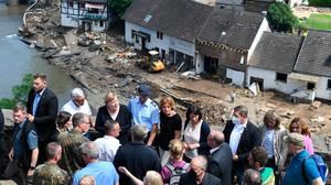 German Chancellor Angela Merkel (3rd L, 1st row) and Rhineland-Palatinate State Premier Malu Dreyer (5th L, 1st row) stand on a bridge during their visit in the flood-ravaged areas to survey the damage and meet survivors on July 18, 2021 in Schuld, near Bad Neuenahr-Ahrweiler, Rhineland-Palatinate state, western Germany