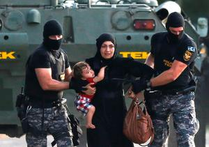 Two Hungarian riot policemen escort a migrant woman and her child in Roszke, Hungary, yesterday. Serbia has condemned Hungary's use of water cannon and tear gas against migrants on their border
