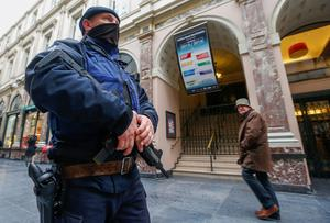 A Belgian police patrols in central Brussels as a civilian walks past. Photo: Reuters