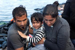 A Syrian refugee boy cries as he is carried by his parents moments after arriving in an overcrowded dinghy at a beach on the Greek island of Lesbos, after crossing a part of the Aegean Sea from the Turkish coast