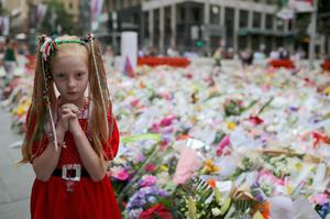 A young girl dressed in Christmas attire walks around the thousands of floral tributes for two deceased hostages Tori Johnson and Katrina Dawson in Martin Place (Getty)