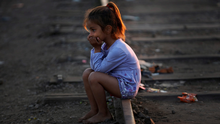 A young syrian girl sits on the tracks at the Serbian border with Hungary as she and her family wait for darkness before heading across country in Hungary. Although shoeless the little girl was in good spiritis.