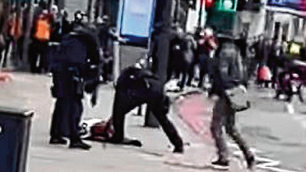 Armed police officers crowd around the attacker after he was shot on the street in Streatham