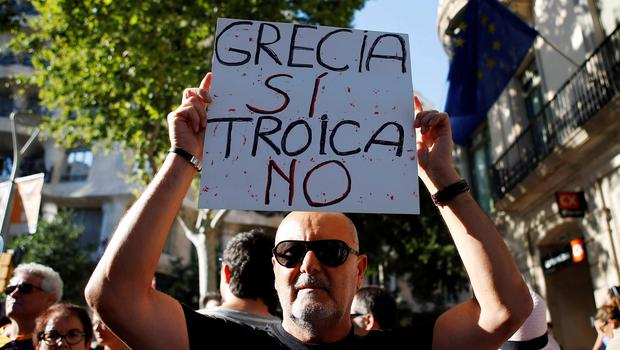 "A man holds a banner supporting Greece during a protest in front of the European Union office in Barcelona, Spain. The banner reads ""Greece yes, Troika no"""