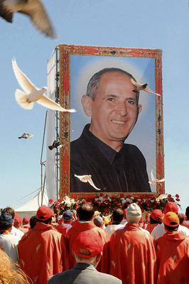Doves fly over the crowd in front of a giant picture of Rev. Giuseppe Puglisi during his beatification ceremony in Palermo, Sicily, southern Italy, Saturday, May 25, 2013. Puglisi, who stirred consciences with his anti-Mafia preaching and was gunned down by mobsters in 1993, has been honored by the Vatican as a martyr. Puglisi urged young people, often jobless and easily recruited by Cosa Nostra, to turn their backs on the mob. (AP Photo/Alessandro Fucarini)