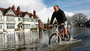 A resident cycles through deep water after the River Thames flooded the village of Datchet, England. Reuters/Eddie Keogh