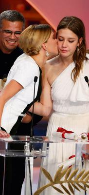 """Actresses Lea Seydoux (C) kisses Adele Exarchopoulos (R) next to director Abdellatif Kechiche (L) after he received the Palme d'Or award for the film """"La Vie D'Adele"""""""