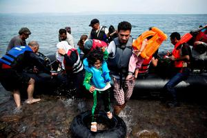 Migrants arrive on a dinghy after crossing from Turkey to Lesbos island, Greece