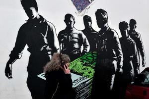 """A woman walks past a mural, entitled """"The Death of Euro"""", by street artist Goin in Athens."""