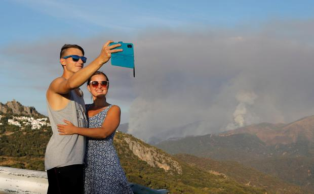 """Tourists take a selfie with clouds of smoke named """"pyrocumulus"""", according to the Andalusian Fire Prevention and Extinction Plan (INFOCA), from a wildfire on Sierra Bermeja mountain, in the background, in Gaucin, Spain, September 10, 2021. REUTERS/Jon Nazca"""