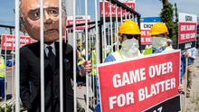 An activist (L) wears a giant mask depicting FIFA President Joseph Blatter inside a cage during a protest by the Avaaz.org organisation prior to the 65th FIFA Congress at the Hallenstadion in Zurich, Switzerland yesterday.