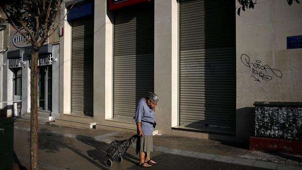 An elderly woman is overcome with emotion outside a Eurobank in Athens yesterday
